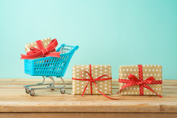 Winter holidays sale concept with gift boxes and shopping cart on wooden table.