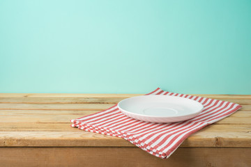 Wooden table with empty plate and tablecloth over blue background
