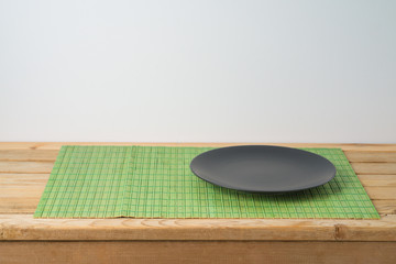 Black empty plate and bamboo placemat on wooden table. Chinese kitchen or restautant concept background