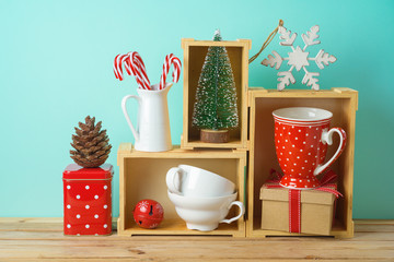 Christmas holiday concept with cups, decorations and pine tree on wooden table.