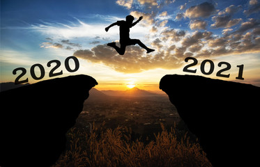 A young man jump between 2020 and 2021 years over the sun and through on the gap of hill ...