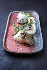 Gourmet fried Japanese skrei cod fish filet with glasswort and furikake onigiri as closeup on a modern design plate