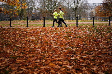 People jog through Hyde Park during autumnal weather in London