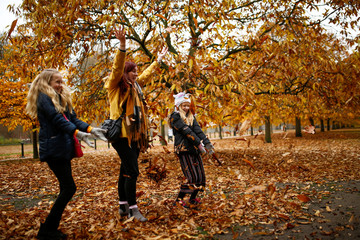 People throw leaves in the air in Hyde Park during autumnal weather in London