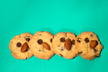 Picture of 4 cookies stack On a turquoise blue background The ingredients are grains without baking powder, contains almonds, pumpkin seeds, chocolate chips, raisins.