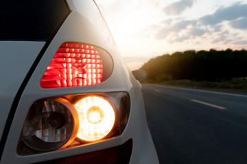 Close up tail lights of white car on asphalt road with sunlight shining in the shadow of nature.