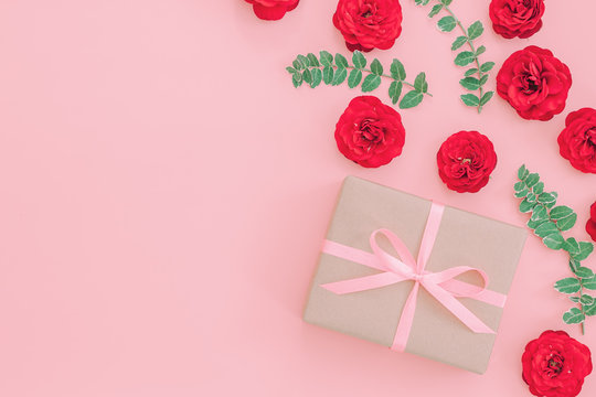 Gift or present box wrapped in kraft paper and rose flower on pi