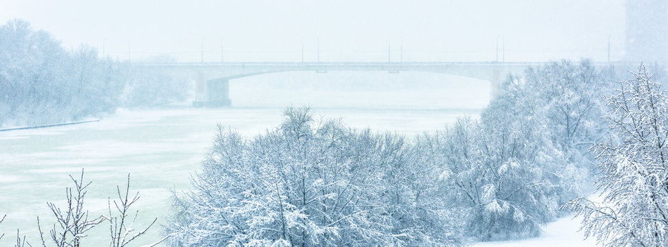 Winter landscape, Moscow, Russia. Scenery of snowy park by frozen Moskva River during snowfall.