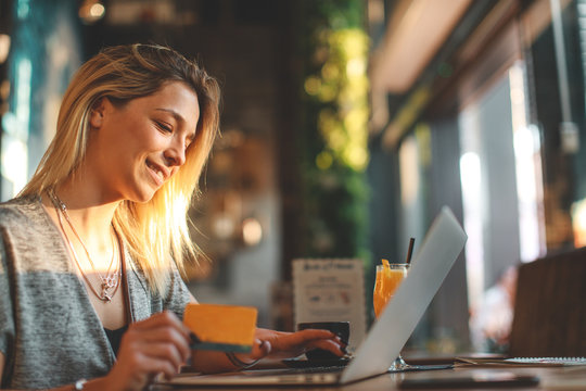 Young woman using credit card shopping online in coffee shop