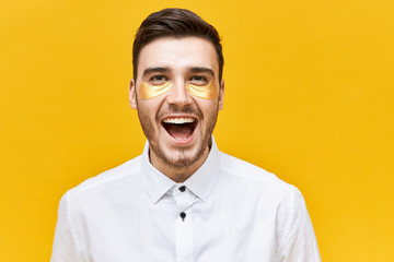 Beauty and skin care concept. Picture of excited joyful young male with stubble wearing golden patches under eyes to look awake and refreshed, screaming with excitement, opening mouth wide opened