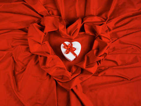 valentines greeting card. white cardboard box in shape of heart wrapped in ribbon lay on a red cloth which repeats the form of present package. love and romance gift concept