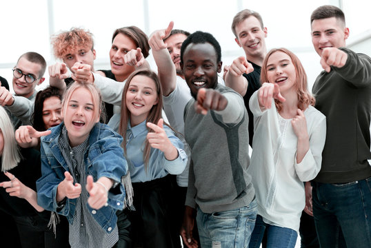 group of cheerful young people pointing at you