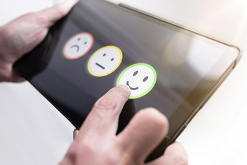 pleased person giving positive feedback by touching smiley face on digital tablet touchscreen, service quality rating concept.