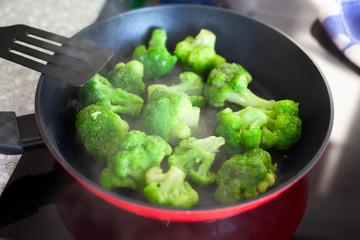 Frying frozen broccoli in a pan