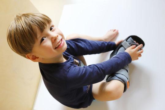 Ein dreijähriger Junge trägt eine Fußorthese