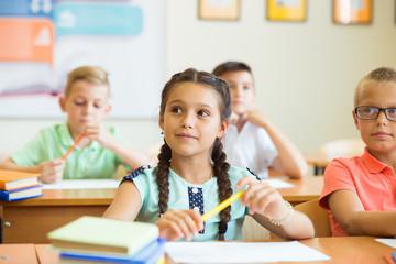 Clever schoolchildren studing and in classroom at school