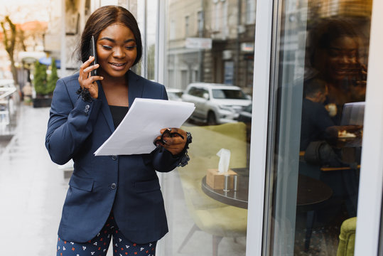 Frowning concerned manager speaking on cellphone outside. Young African American business woman standing near outdoor glass wall. Mobile phone talk concept