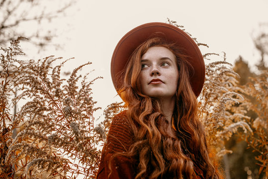 Outdoor close up portrait of young attractive redhead girl with natural freckled skin, long curly hair, wearing stylish orange hat, posing in beautiful autumn nature. Copy, empty space for text