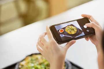 A girl take a picture of some food by smartphone in restaurant
