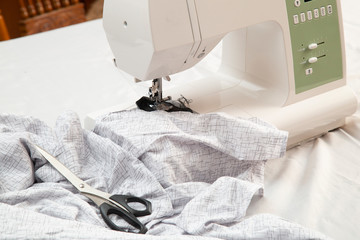 Modern sewing machine is used at home for sewing clothes.