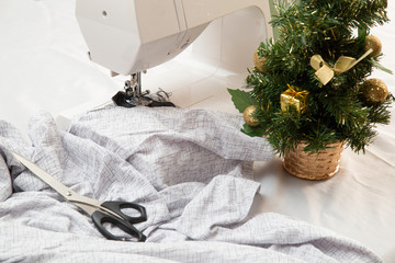 Christmas, small business.Modern sewing machine is used at home for sewing clothes.