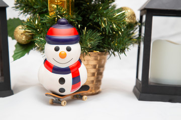 Christmas card with a Christmas tree and a snowman on a snowboard.