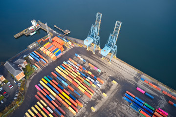 Containers and cranes at logistics port terminal with many colours aerial view from above