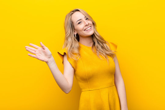 young pretty blonde woman smiling happily and cheerfully, waving hand, welcoming and greeting you, or saying goodbye against flat color wall