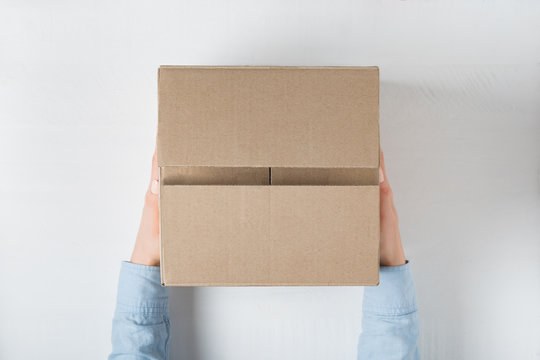 Large square cardboard box in female hands. Top view, white background