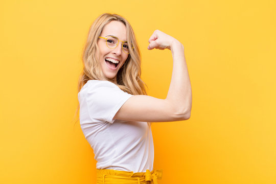young pretty blonde woman feeling happy, satisfied and powerful, flexing fit and muscular biceps, looking strong after the gym against flat color wall