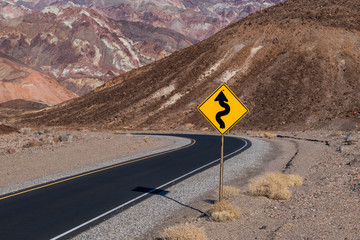 A crooked road sign along a highway curving through a barren and rugged desert landscape