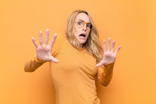 young pretty blonde woman feeling terrified, backing off and screaming in horror and panic, reacting to a nightmare against flat color wall