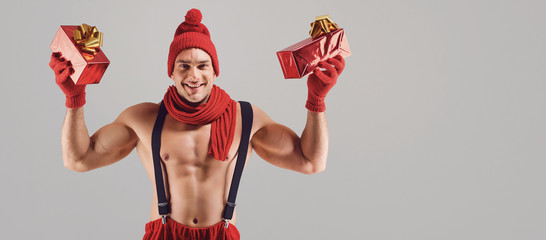 Athletic man with gifts smiling at christmas.