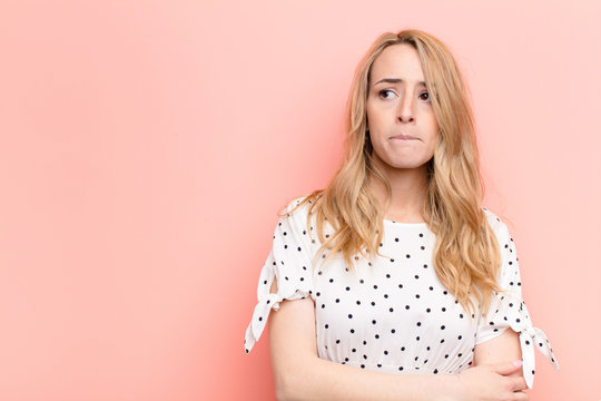 young pretty blonde woman doubting or thinking, biting lip and feeling insecure and nervous, looking to copy space on the side against flat color wall