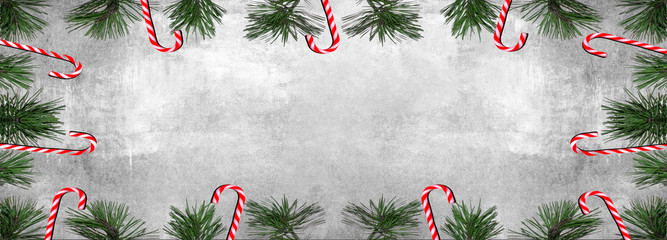 Christmas background panorama banner long - Frame made of sweet candy canes and pine branches isolated on gey concrete stone texture - top view with space for text