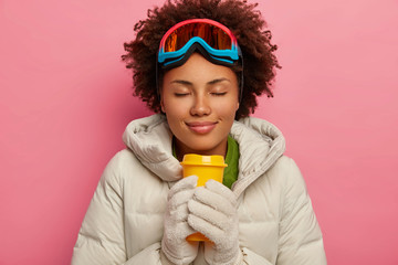 Beautiful relaxed curly haired girl in white coat and gloves, enjoys hot aromatic drink, wears snowboard mask, has sporty winter holidays, isolated over pink background. Ski adventure and pastime
