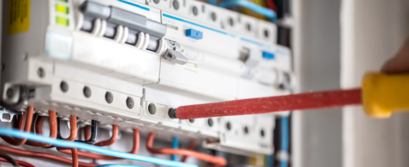 Man, an electrical technician working in a switchboard with fuses. Installation and connection of electrical equipment. Close up.