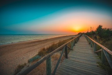 Fototapeten Dunkelbraun Beautiful wooden pier on the beach with sunset in the background captured in Andalucia, Spain