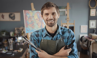 Portrait of young bearded artist in checked shirt with a smoking pipe in a painting atelier