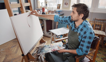 Inspired male artist in blue checked shirt making a first stroke of his new painting in a light loft studio