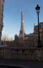 View of the Eiffel Tower from a small cobbled dead-end street at sunny autumn afternoon. Paris.