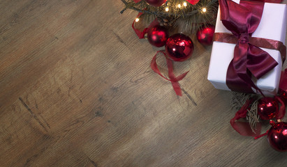Top view of a Christmas decorated background with a present, tree, and flashing lights on a wooden desk. With copy space for your new year wishes