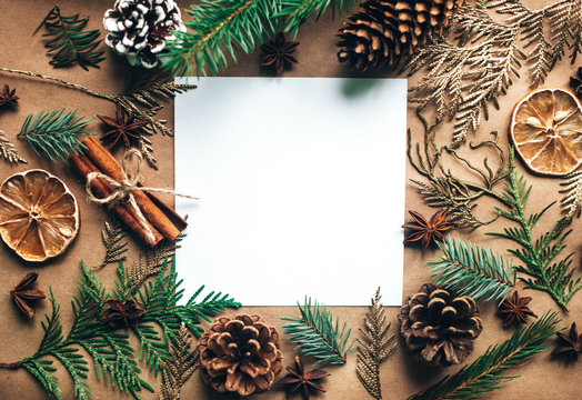 Natural Christmas decorations made of wood and pinecones without plastic. Gifts. Blank white paper sheet. Zero waste Christmas, concept flat lay.