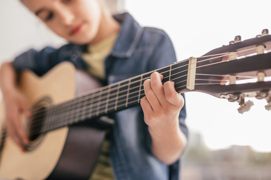 Blurred kid learning to play guitar