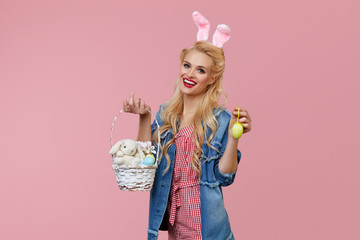 Happy Easter. Beautiful young woman with bunny ears and basket full of Easter eggs on pink background. Pin up and retro style fashion.