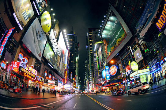 NEW YORK CITY, FEB 5: The famous 42nd Street in NYC at night with its famous neon signs and traffic near the Times Square through fisheye lens - artistic image, NYC, Feb 5, 2016 USA