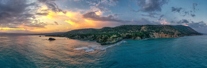 Wonderful panoramic landscape with amazing sunrise. Rocky coast and mountains. Shot from a height from the sea. Cyprus