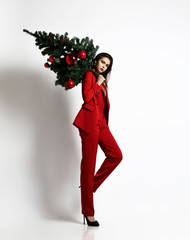 Beautiful brunette girl in a stylish red office jacket and trousers walks and carries a Christmas...