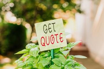 Text sign showing Get Quote. Business photo text the most recent price to which a buyer and seller agreed Plain empty paper attached to a stick and placed in the green leafy plants