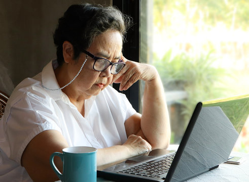 Asian senior woman sitting by the windor with blue cup of coffee and computer laptop on table , looking thoughfully at computer screen
